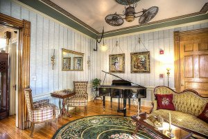 Couch, chessboard, piano, and paintings in living room