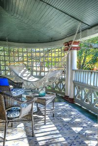 Wicker furniture and hammock hung in wood deck