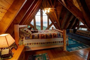 Quilted bed and couch under vaulted wood ceiling
