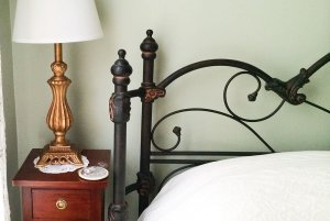 Metal frame of bed next to bedside lamp