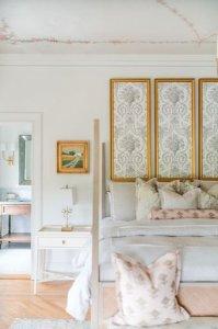 Gold framed art above king bed
