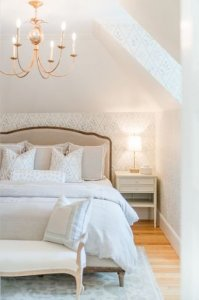 King bed with gold chandelier hanging above