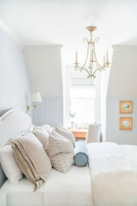 Bed with gold chandelier hanging above