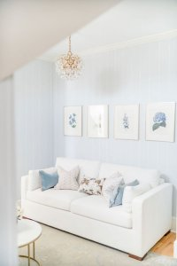 Couch with blue pressed flower art hanging above