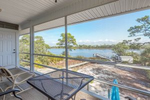 Screened balcony overlooking yard and water