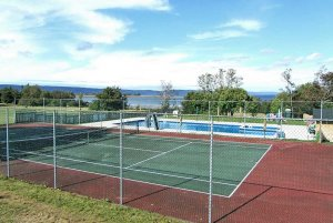 Fenced tennis court by pool