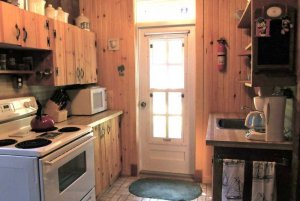 Kitchen with stove, door, and cabinets