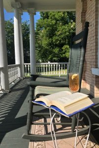 Front porch with chair, table, and book