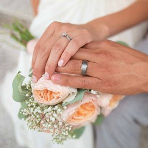 bride and groom showing their rings