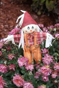 Small scarecrow doll in flowers