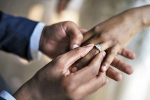 man placing ring on woman's finger