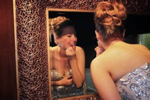 bridesmaid putting on makeup in mirror