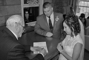 bride and groom, man signing wedding certificate