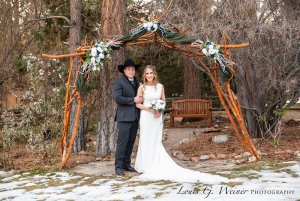 Bride and groom standing beneath archway