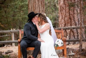 Bride and groom kissing on outdoor bench
