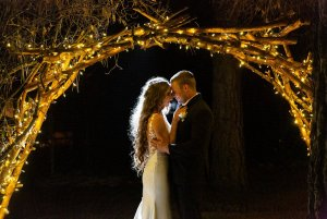 Bride and groom holding each other beneath the lights