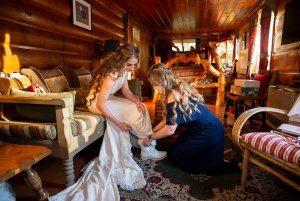 Bridesmaid helping bride prepare for ceremony