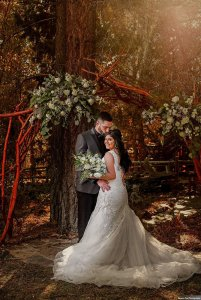 Groom holding bride under flowers at the altar