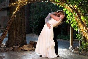 Groom dipping bride under archway