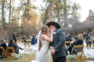 Bride and groom kissing near guests in the snow