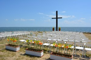 Black Walnut Point Weddings seats cross at the altar by the water