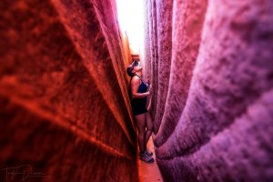 A woman turned sideways to fit through a narrow slot canyon