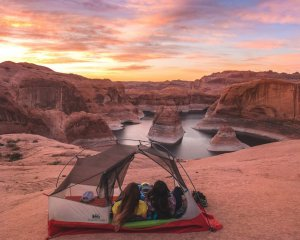 Two women in a tent overlooking a water-filled canyon
