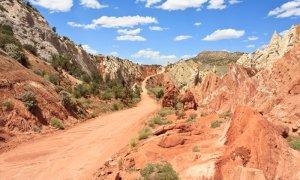 A dirt road winding upwards through a rocky canyon