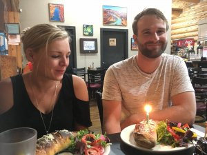 A couple at a restaurant with a birthday candle on one plate