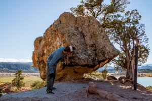 A man peering around the side of a boulder