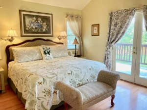 A bed with white covers and floral decor