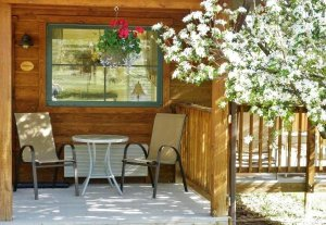 Two chairs and a small table on a shaded porch