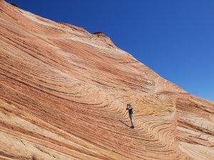A photographer standing on a layered rock hillside
