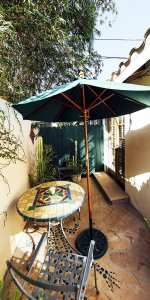 An outdoor patio with a table and shade umbrella