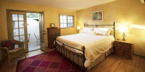 A bedroom with an open door to a walled patio
