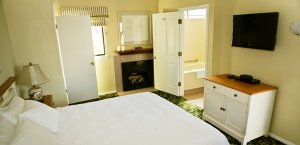 Cottage King Whirlpool Room with bed, fireplace, and dresser