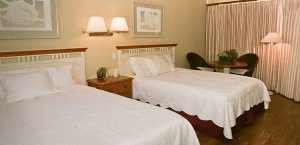 Two queen beds with night stand, two chairs and a table