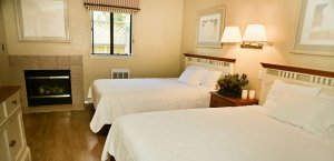 Two Queen Beds with lamps and fireplace