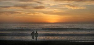 Couple on the beach at sunset in Cambria, California