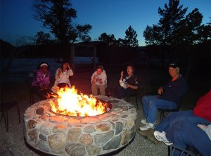 A group of people gathered around a campfire in a firepit