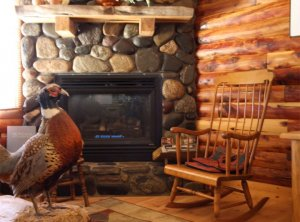 A chair and a pheasant decoration near a fireplace