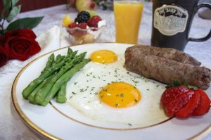 eggs, sausage, asparagus, sliced fruit, a yogurt parfait, orange juice, and coffee