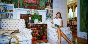 A girl reading on a loveseat