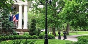 Pillared porch near grass and shade trees