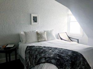 A bed near a sunlit window