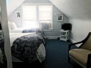 Two beds and a television near a window