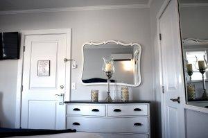 A mirror over a dresser