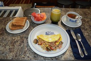 A breakfast with an omelet, melon cubes, toast, orange juice, and tea