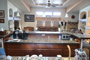 A kitchen island with coffee machine and other amenities