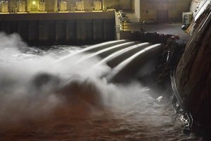 Water spraying from behind a dam at night